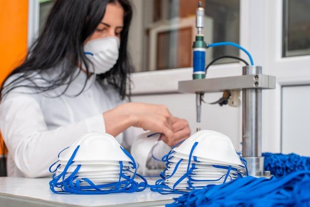 Una donna lavora in una macchina per la produzione di maschere mediche con nanofibre e anelli di saldatura con ultrasuoni.