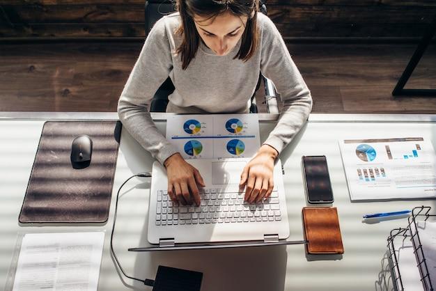 La donna lavora in ufficio con il computer portatile al tavolo di lavoro.