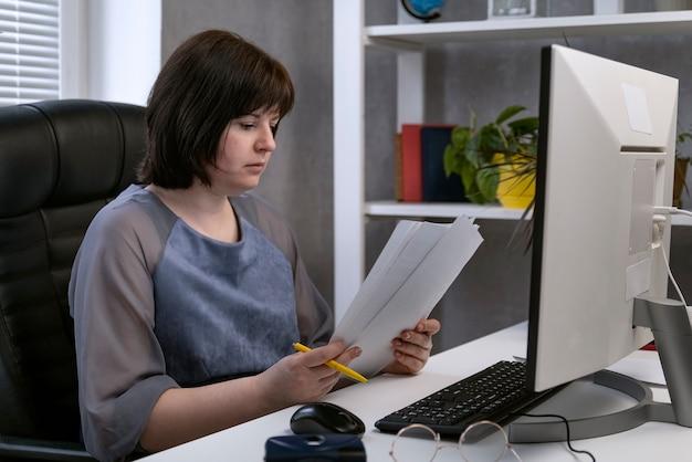 La donna lavora con i documenti sul posto di lavoro nel proprio gabinetto. il direttore sta leggendo i contratti. lavoro d'ufficio.
