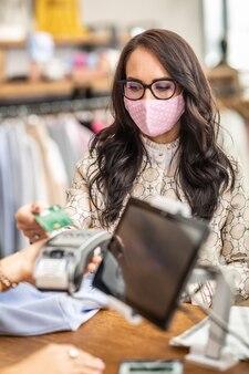 La donna preoccupata per il coronavirus paga senza contatto con una carta nel negozio che indossa una maschera facciale.