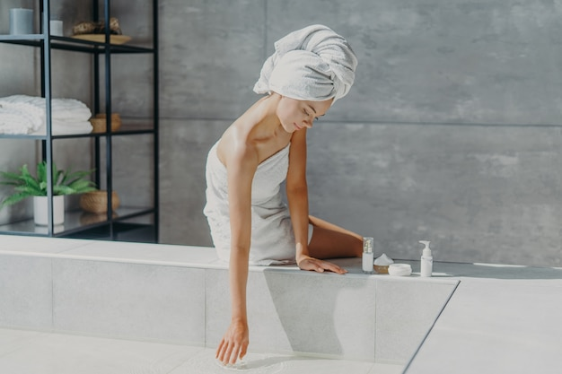 La donna avvolta in un telo da bagno utilizza prodotti cosmetici per prendersi cura del corpo che va a fare il bagno