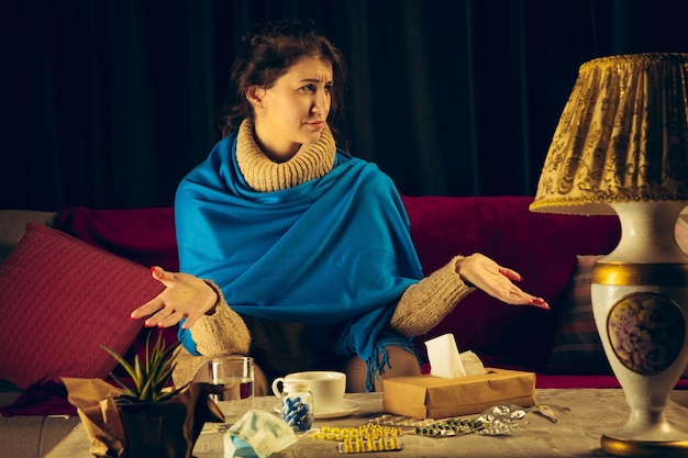 La donna avvolta in un plaid sembra malata, malata, starnutisce e tossisce seduta a casa in casa