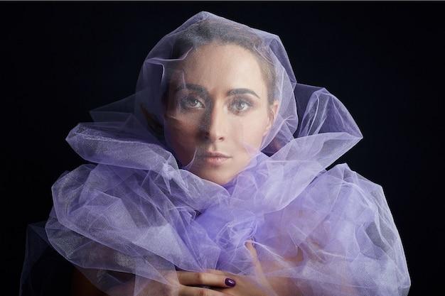 Donna avvolta in tessuto viola, bella figura snella, purezza e integrità. perfetta cura della pelle del viso, cosmetici naturali. arte di donna nuda in abito trasparente chiaro lilla in posa su uno sfondo scuro