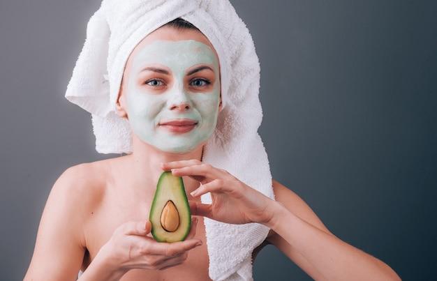 Donna avvolta in un asciugamano con una maschera cosmetica sul viso e avocado nelle sue mani
