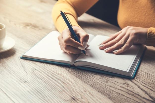 La donna scrive in un taccuino sul tavolo