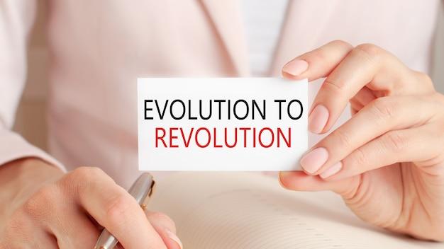 La donna scrive in un taccuino con una penna d'argento e una carta della stretta della mano con il testo: evoluzione alla rivoluzione.