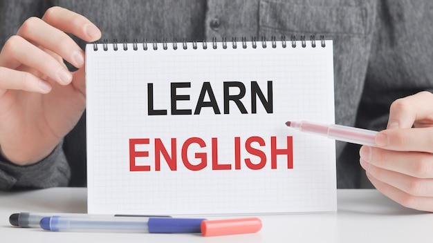 La donna scrive in un taccuino con una penna d'argento e una carta della tenuta della mano con il testo: impara l'inglese. superficie rosa