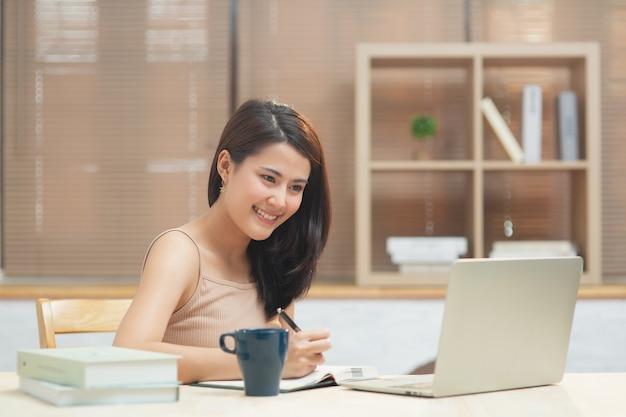 Donna che scrive in agenda mentre guarda sul laptop