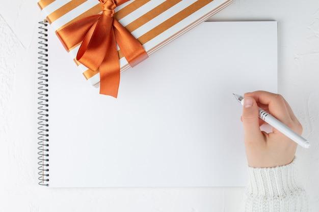 Scrittura della donna sul taccuino in bianco fra il contenitore di regalo. vista piana laico e dall'alto
