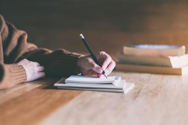 Scrittura della donna sul taccuino in bianco sulla tavola di legno