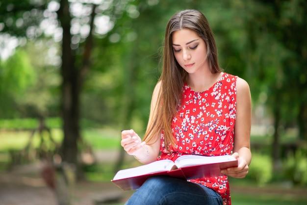 Donna che scrive su un libro in un parco
