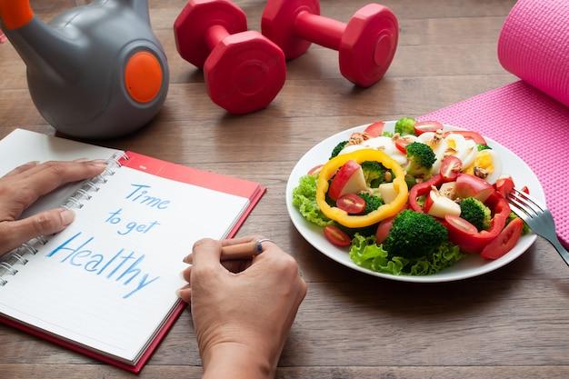 Scrittura della donna sul libro del diario con attrezzature per il fitness e insalata sul tavolo