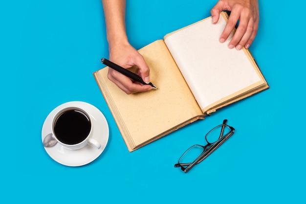 Donna che scrive in un diario con una tazza di caffè su uno sfondo blu in una vista dall'alto
