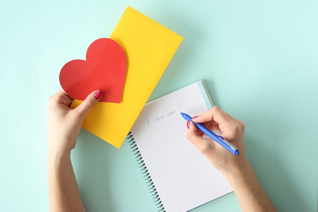 Lettera di scrittura della donna con la penna a sfera per il primo piano di giorno di biglietti di s. valentino