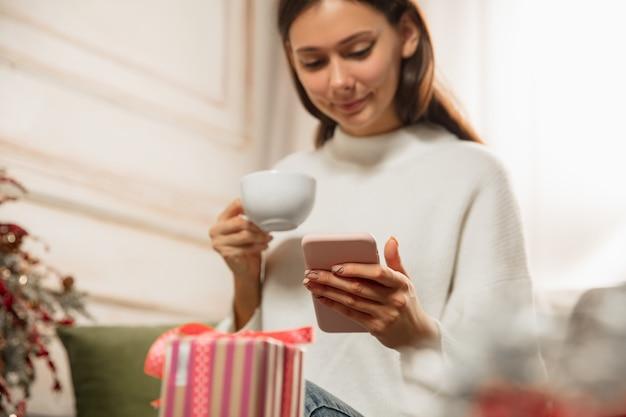 Messaggio di scrittura della donna, auguri per il nuovo anno e natale 2021 per amici o familiari con il suo cellulare. entrare in contatto utilizzando i dispositivi. vacanze, celebrazione. sembra allegro, felice, attento.