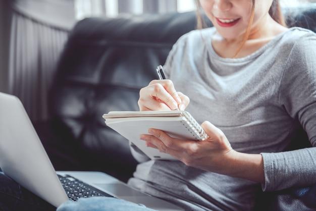 Donna che scrive sul taccuino e utilizza il computer portatile sul divano.