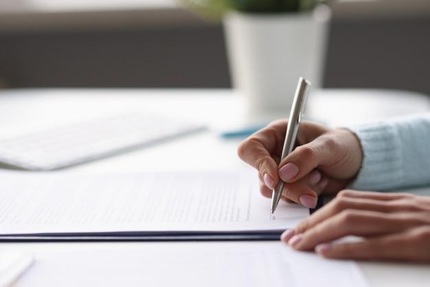Donna che scrive con penna a sfera in documenti a tavola a casa primo piano lavoro a distanza con documenti