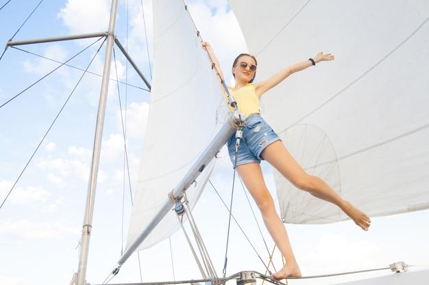 Una donna su uno yacht sullo sfondo di vele bianche e il cielo concetto di una gita in barca