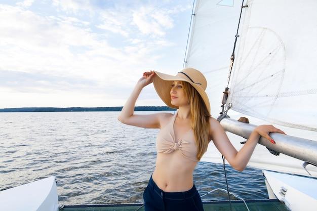 Una donna su uno yacht contro lo spazio di una vela e un cielo blu. concetto di ricreazione e viaggio in mare.