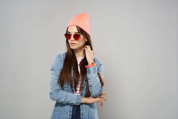 Donna in occhiali gialli moda cappello rosa in stile moderno sfondo grigio
