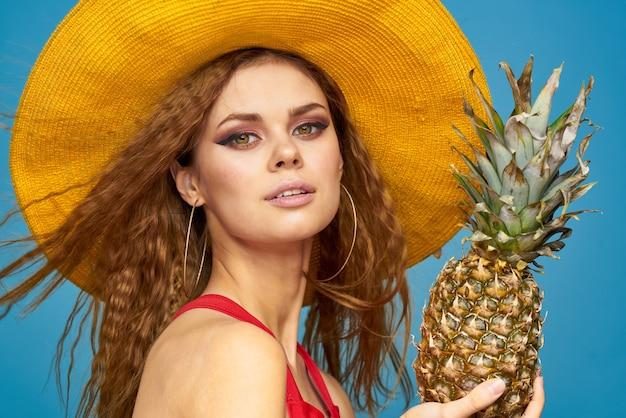 Donna in cappello giallo con ananas mani capelli ricci frutti esotici sfondo blu aspetto attraente. foto di alta qualità