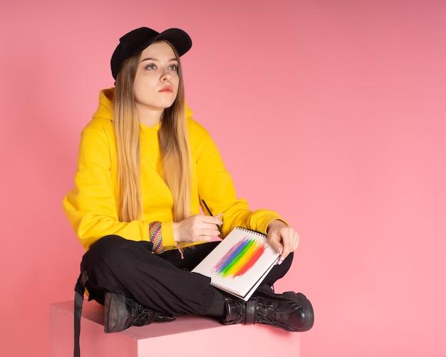 Donna in felpa con cappuccio gialla, berretto nero con trafitto al naso, che dipinge un arcobaleno lgbtq