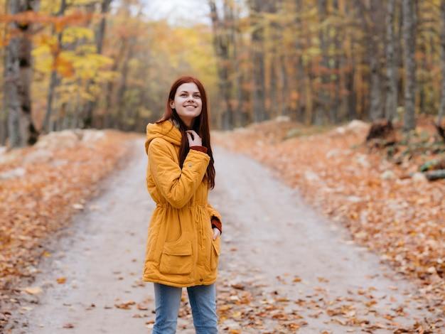 Donna in giacca gialla con foglie autunnali viaggio viaggio nella foresta. foto di alta qualità