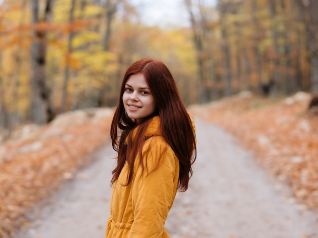 Donna in giacca gialla strada forestale autunno viaggiatore aria fresca