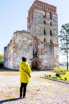 La donna in una giacca gialla guarda il vecchio edificio in rovina del tempio
