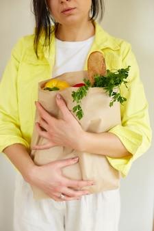 Donna in giacca gialla, in piedi con il sacchetto di carta della spesa