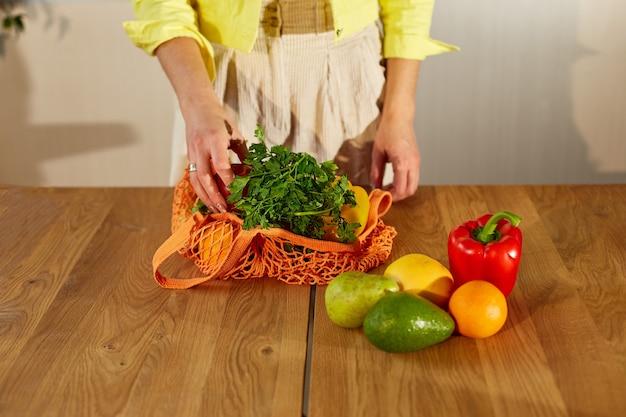 Donna in giacca gialla disimballaggio borsa eco rete shopping con frutta e verdura sane in cucina