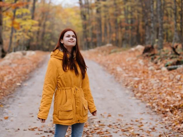 La donna in una giacca gialla cammina nell'aria fresca della foresta autunnale