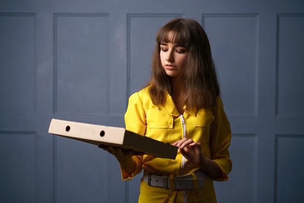 Donna in tuta gialla consegna pizza. il concetto di piccola impresa