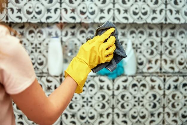 La donna in guanti di gomma gialli pulisce la cabina doccia in vetro del bagno