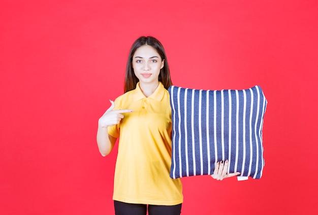 Donna in camicia gialla che tiene un cuscino blu con strisce bianche.