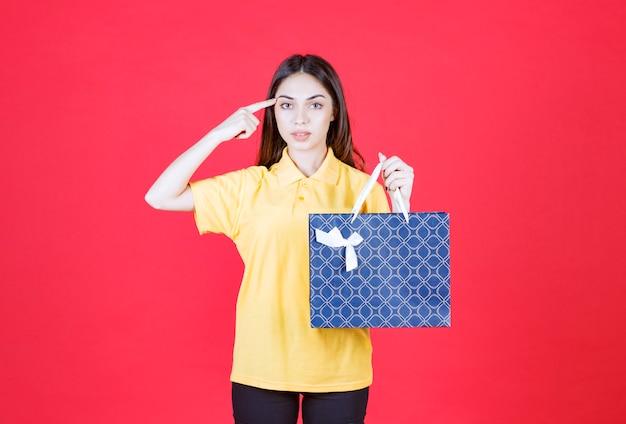 Donna in camicia gialla che tiene una borsa della spesa blu e sembra confusa e premurosa.