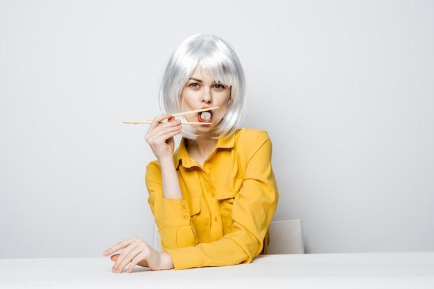 Donna in camicia gialla che si siede al cibo asiatico del ristorante dello spuntino della tavola