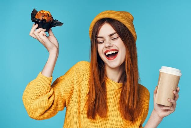 Donna con un maglione giallo e un berretto con una tazza di caffè cupcake in mano uno spuntino