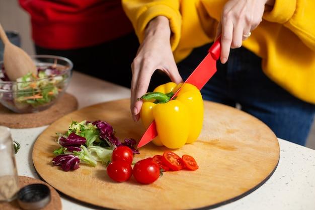 Donna in maglione giallo che tiene un coltello rosso affilato durante il taglio della paprica gialla grande. pomodorini e lattuga sul tagliere vicino