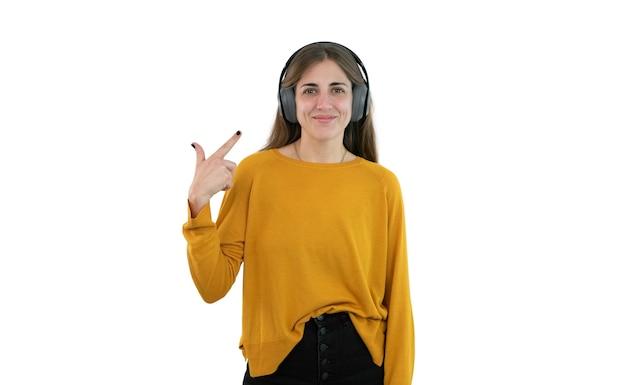 La donna in maglione giallo che ascolta la musica con le cuffie senza fili, sta indicando con il suo dito isolato su priorità bassa bianca.