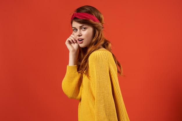Donna in maglione giallo con fascia rossa alla moda