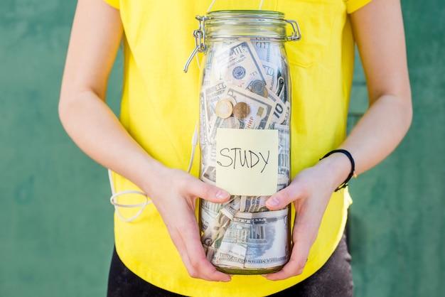 Donna in maglietta gialla che tiene una bottiglia con risparmi di denaro per lo studio