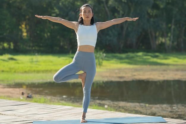 Donna su una stuoia di yoga per rilassarsi nel parco al lago di montagna. attraente ragazza sportiva in abiti sportivi. ragazza sportiva che lavora fuori. stile di vita sportivo sano. giovane donna atletica nel fare esercizio di fitness.