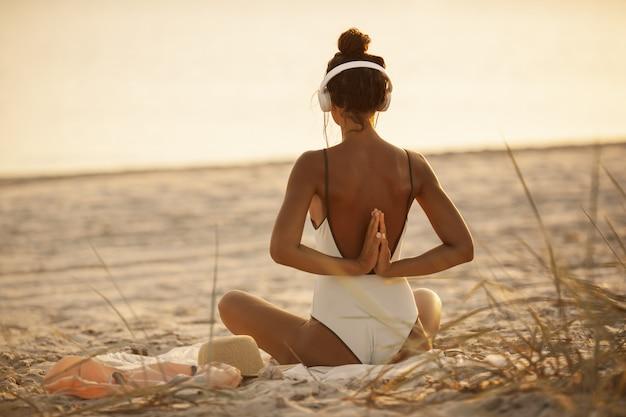 Donna nella posa di meditazione di yoga con le cuffie sulla spiaggia