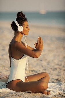 Donna in posa di meditazione yoga con le cuffie sulla spiaggia