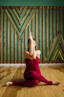 Yogi donna in abiti sportivi marrone si siede nell'asana vatayanasana nella stanza