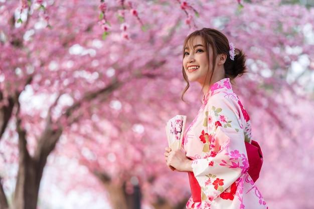 Donna in yukata (abito kimono) con ventaglio pieghevole e guardando sakura fiore o fiore di ciliegio in fiore nel giardino