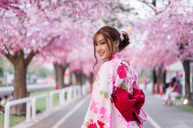 Donna in yukata (abito kimono) alla ricerca di fiori di sakura o fiori di ciliegio in fiore nel giardino