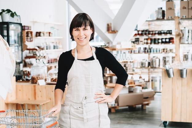 Donna in un negozio a rifiuti zero venditore assistente in un negozio senza plastica proprietario di successo piccola impresa