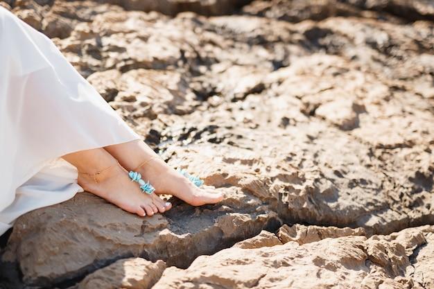 Womans piedi nudi con elegante pedicure e braccialetti sulle rocce closeup donna seduta sulla roccia
